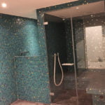 Badzimmer mit Mosaiksteinen und Duschkabine